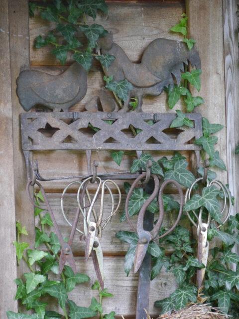 Alte Bonsai-Scheren als Dekoration an der Hüttenwand von Wurzerls Garten.