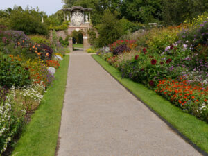 Doppel-Mixed-Border, Nymans Garden, mit Mauer-Tor