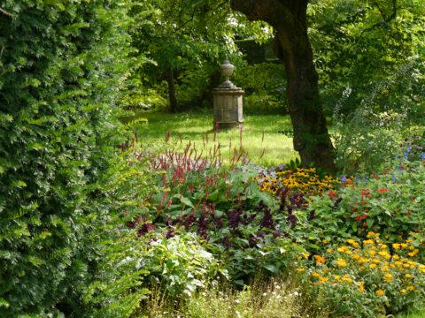 Blick vom Doppel-Mixed-Border zu einem der Familien Memorial, Nymans Garden