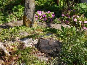 Steingartenende und Beet vor der Gartenhütte in Wurzerlsgarten