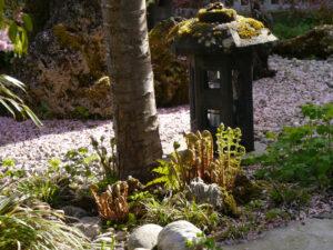 Alte Steinlaterne am Rand der Kranichinsel im Vorgarten von Wurzerlsgarten
