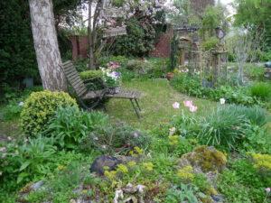 Blick vom Steingarten bis zur roten Klinkermauer am anderen Gartenende in Wurzerlsgarten