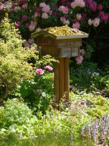 Blick zum Insektenhotel vor der Rhododendronsenke in Wurzerlsgarten