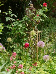 ein Pfosten des Paradiestores, mit Allium, Centranthus ruber und den ersten Rosenblüten von 'Dark Lady' in Wurzerlsgarten